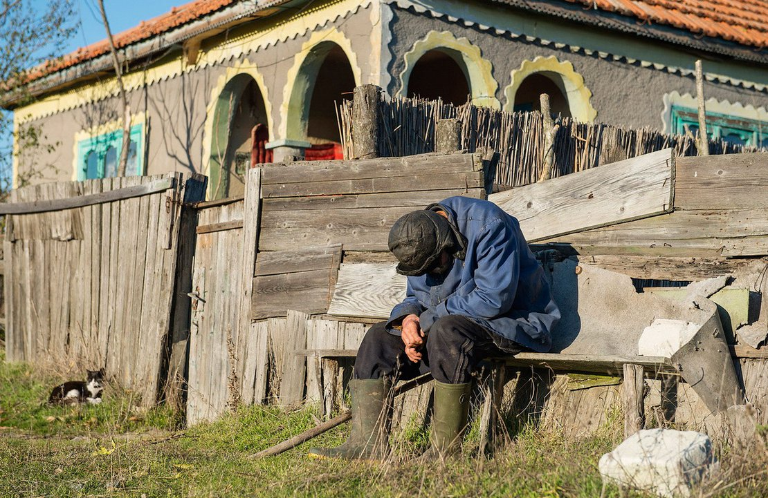 An old man rests in front of his house in Sfistofca, the Danube Delta, Romania