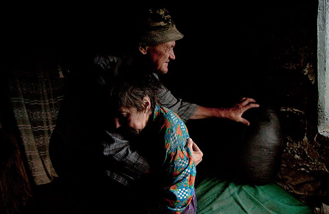 Achim, a blind man, helps his paralyzed wife, Maria, to stand so he can feed her. Sfistofca, Romania, 2012.