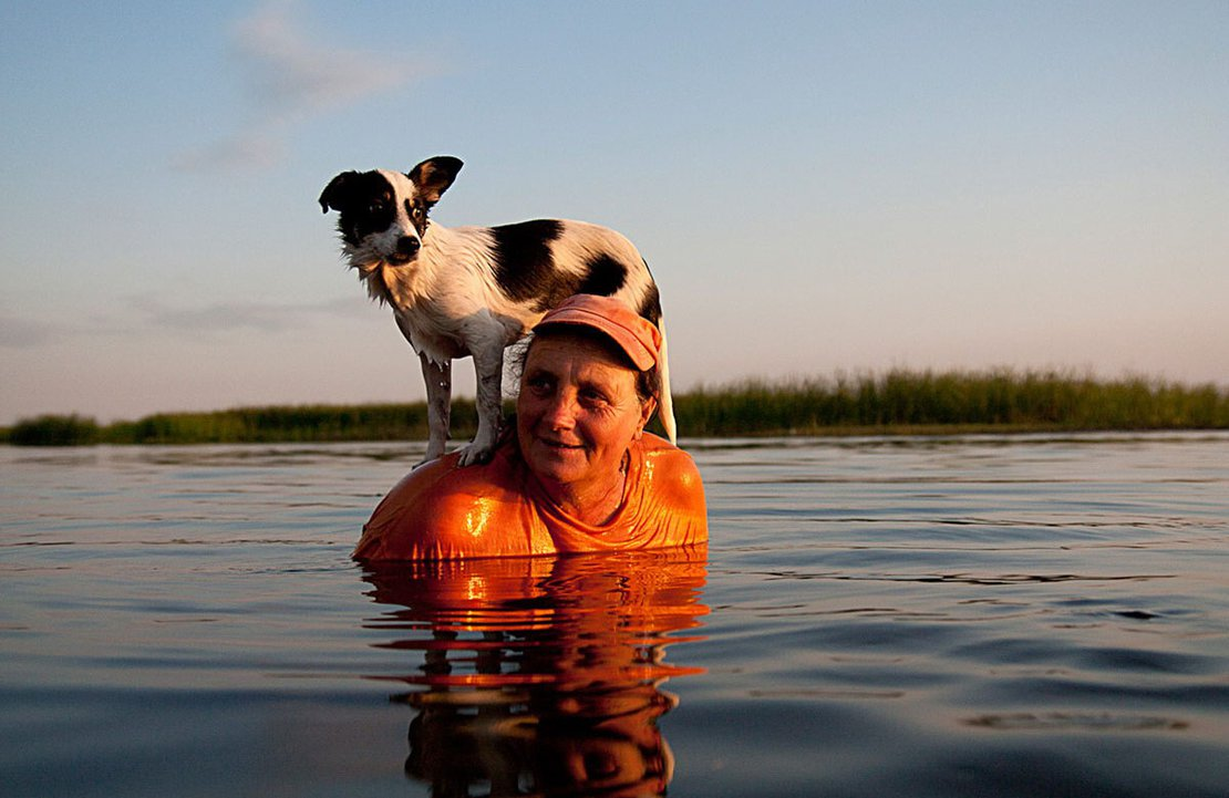 A woman and her companion escape the scorching July sun in the channel near the village. Letea, Romania, 2011.