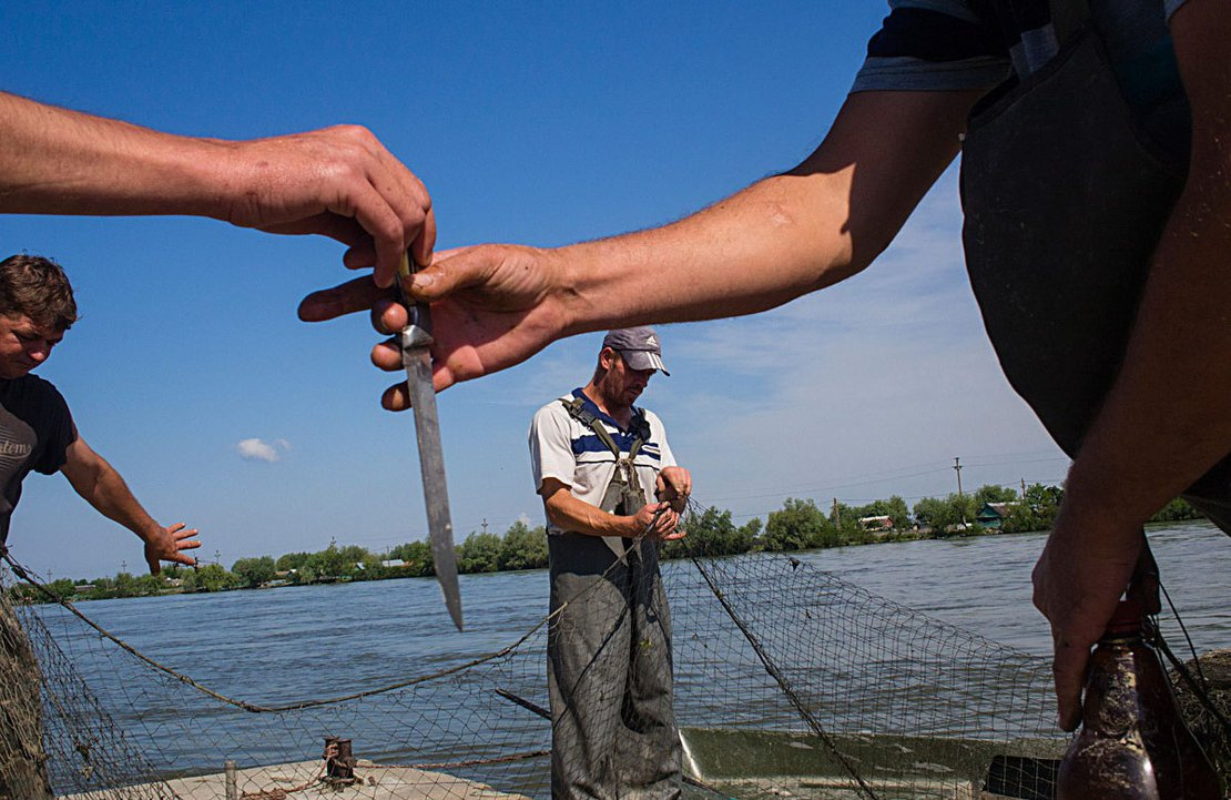 Fishermen disentangle and clean they nets. Sulina, Romania, 2013.
