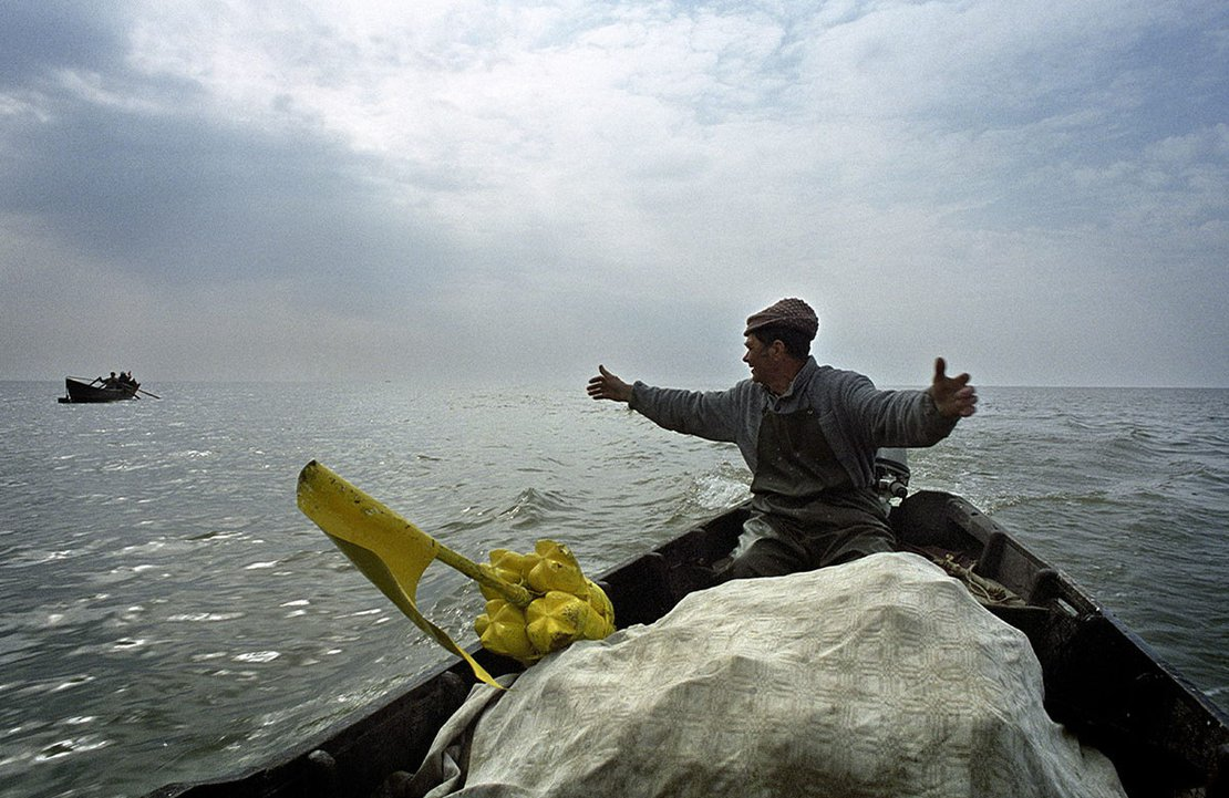 A playful fishermen returning home after working shows to the others the size of fish he got today, Sfantu Gheorghe